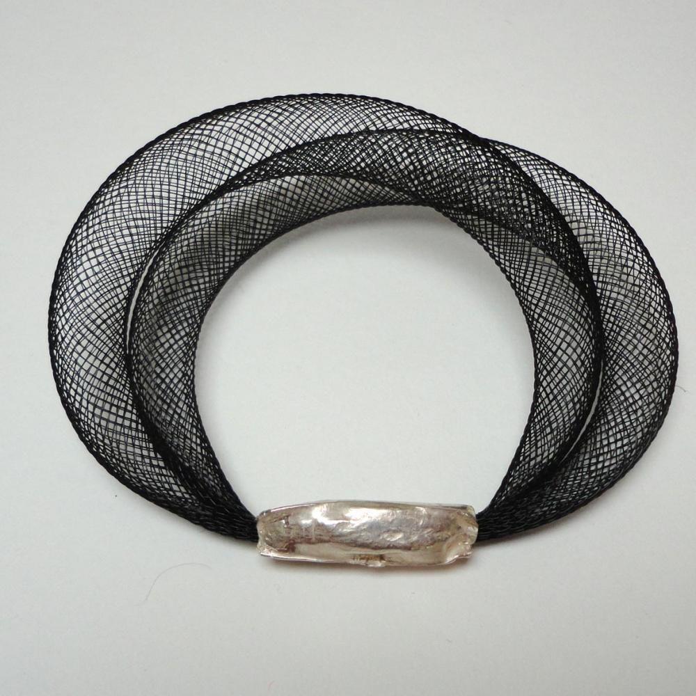 Black PVC stent with fold formed silver bracelet